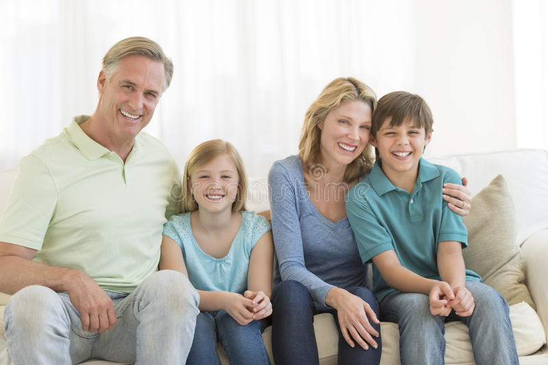 Familie van Vier die samen op Bank glimlachen royalty-vrije stock foto