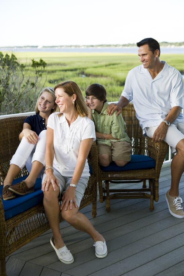 Familie van vier die samen in openlucht op terrac zitten stock afbeelding