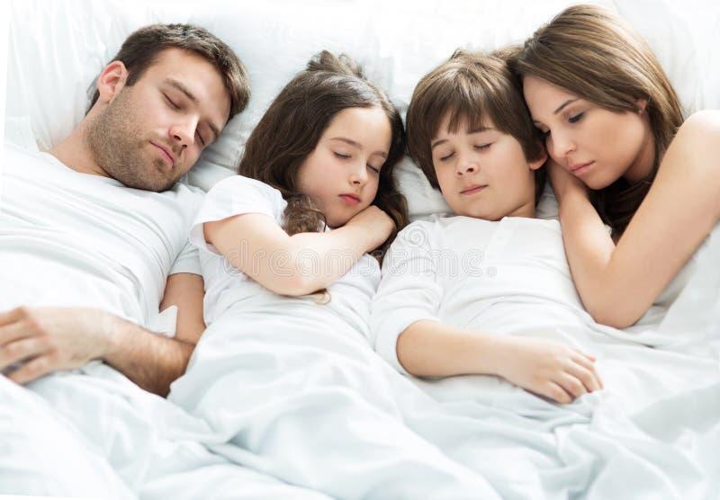 Familie van vier die slapen stock fotografie