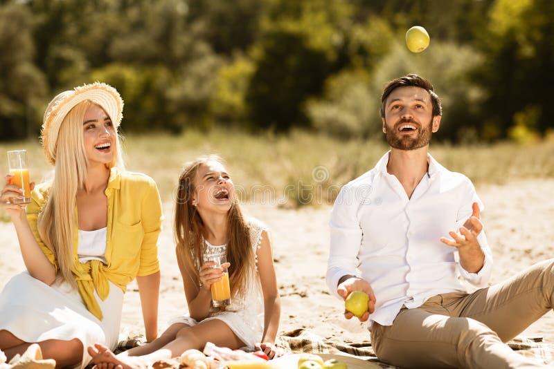 Familie van vier in het de herfstbos Vader het jongleren met met appelen, die pret hebben royalty-vrije stock afbeeldingen