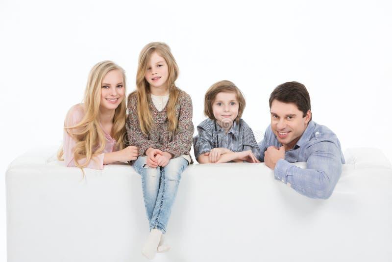 Familie van vier op een bank thuis royalty-vrije stock afbeelding