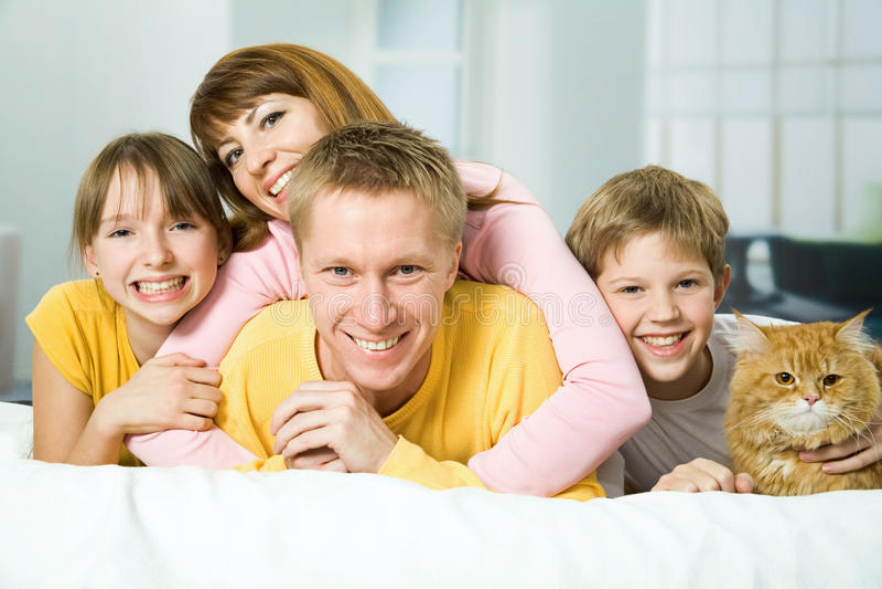 Familie van vier op een bed stock afbeelding