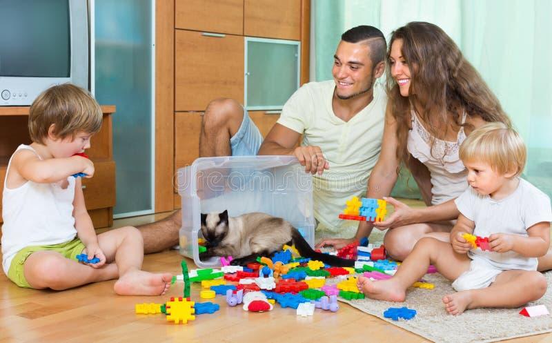 Familie van vier thuis met speelgoed stock fotografie