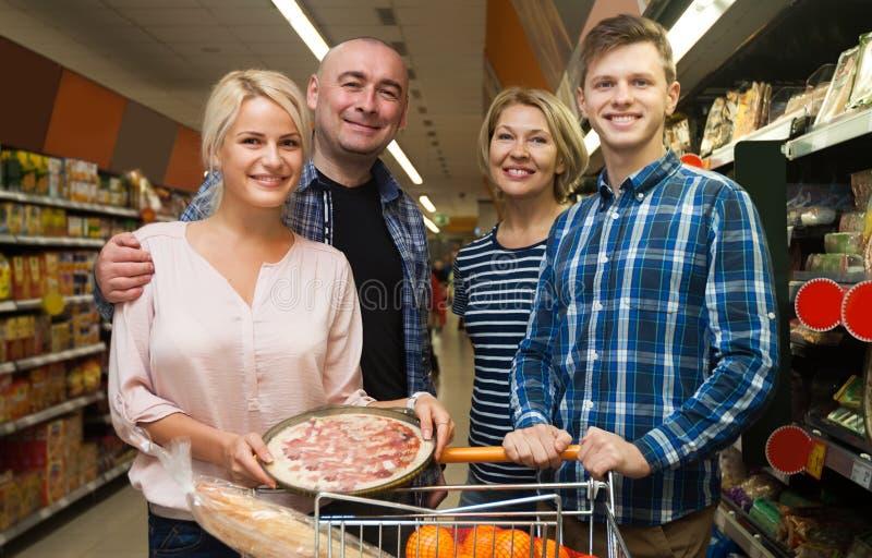 Familie van vier volwassenen in de supermarkt royalty-vrije stock foto