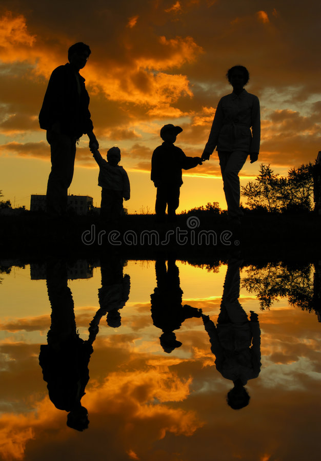 Familie van vier zonsondergangwater