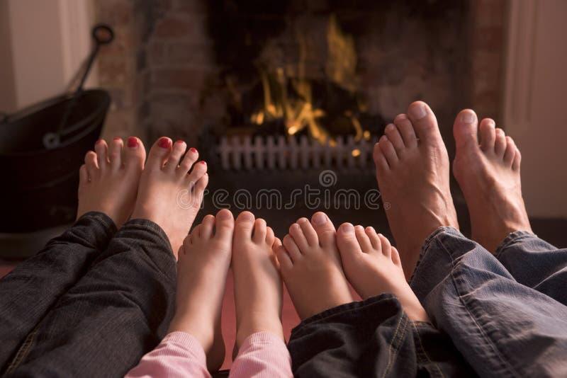 Familie van voeten die bij een open haard verwarmen stock afbeeldingen