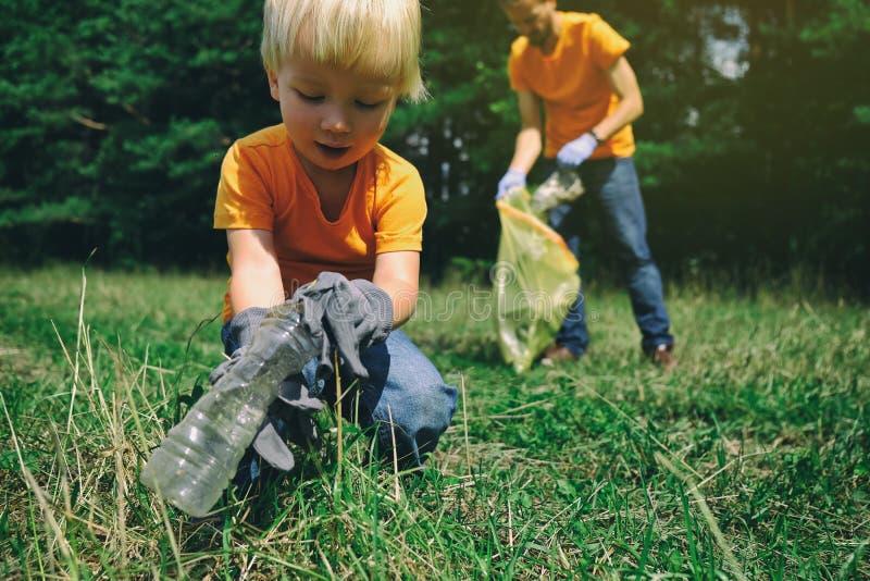 Familie van vrijwilligers met kinderen die huisvuil in park verzamelen Sparen milieuconcept Weinig jongen en zijn vader schoonmak stock foto