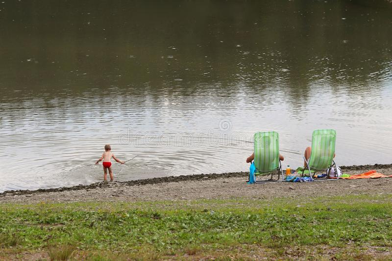 Familie: Vater, Mutter und Sohn stehen auf Strandstühlen auf dem Ufer durch den Teich still Familienurlaub auf dem Wasser Strand  lizenzfreie stockfotografie