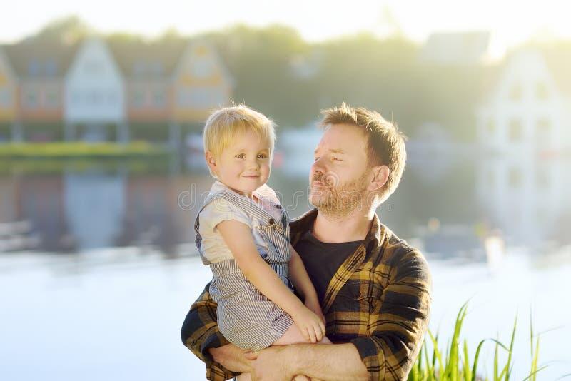 Familie, Vater und kleiner Sohn, auf dem Hintergrund von idealistischen Häusern auf dem See Träume des Hauses lizenzfreies stockbild