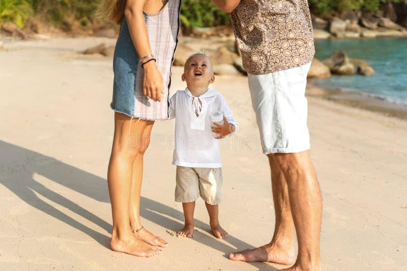Familie verliefd op het strand met de zoon wordt gespeeld stock afbeeldingen