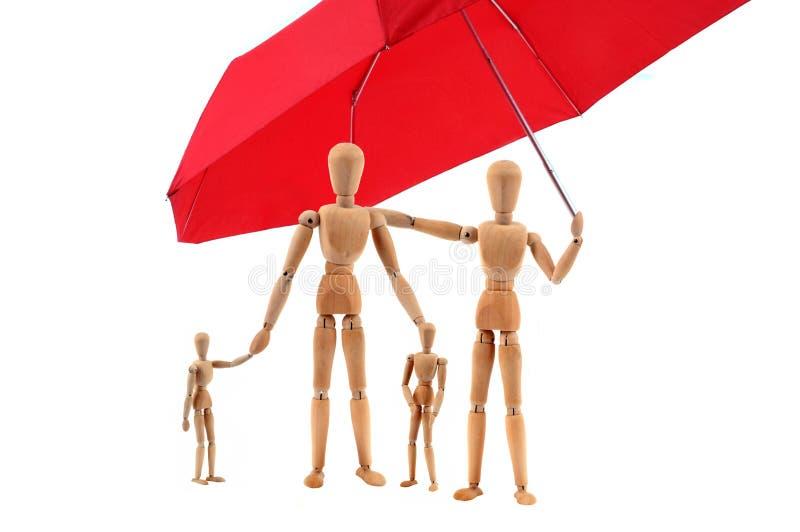 Familie von den gegliederten hölzernen Attrappen geschützt durch einen Regenschirm lizenzfreies stockbild