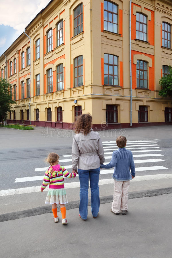 Familie von drei und Überfahrtstraße lizenzfreies stockbild