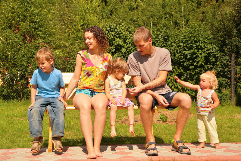 Familie von fünf sitzen auf Bank stockfotografie