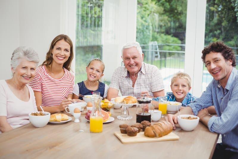 Familie von mehreren Generationen, die bei Tisch während des Frühstücks sitzt lizenzfreies stockbild