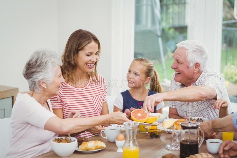 Familie von mehreren Generationen, die Früchte während des Frühstücks isst lizenzfreie stockfotografie