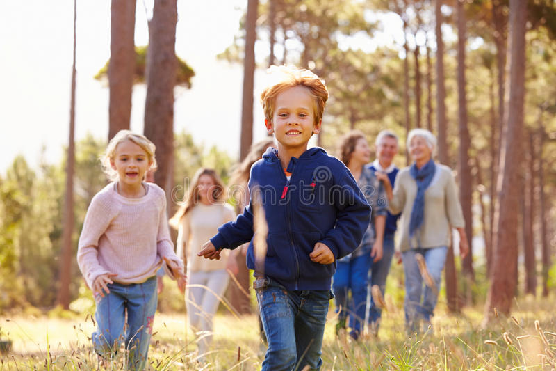 Familie von mehreren Generationen, die in Landschaft, Kinderlaufen geht lizenzfreie stockbilder