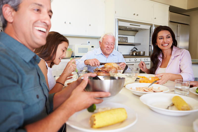 Familie von mehreren Generationen, die um die Tabelle isst Mahlzeit sitzt stockbild