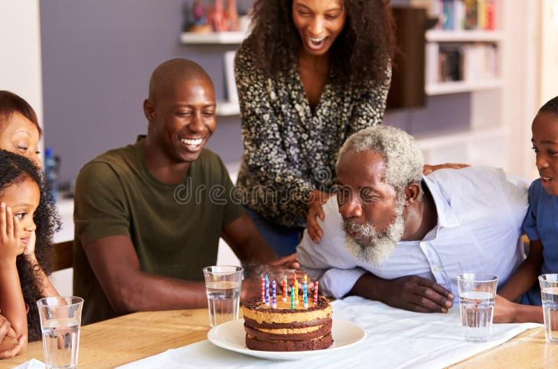 Familie von mehreren Generationen, die zu Hause Großvater-Geburtstag mit Kuchen und Kerzen feiert lizenzfreie stockfotografie