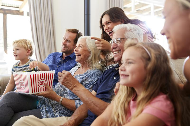Familie von mehreren Generationen, die zusammen auf Sofa At Home Eating Popcorn und aufpassendem Film sitzt stockfotos