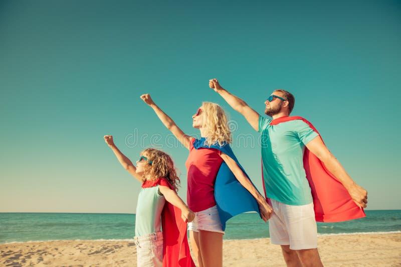 Familie von Superhelden auf dem Strand Reisenkoffer mit Meerblick nach innen lizenzfreie stockfotos