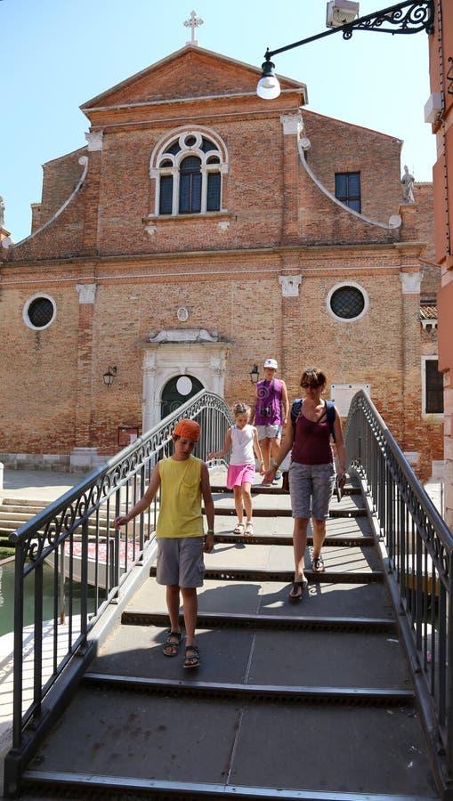 Familie von Touristen auf der Brücke nahe bei einer Kirche in der Stadt von lizenzfreies stockfoto