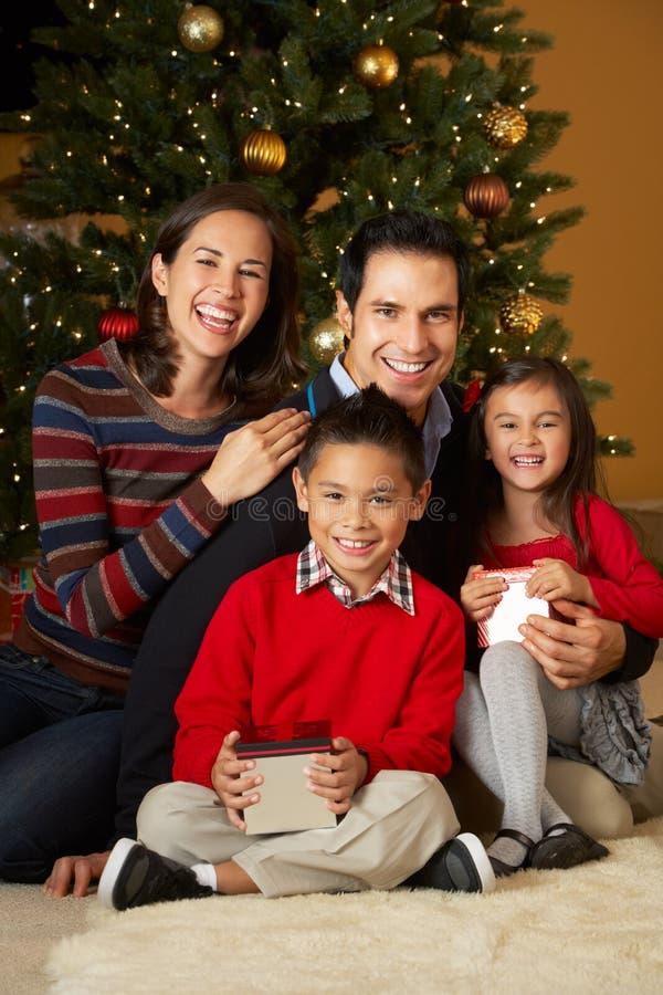Familie vor Weihnachtsbaum lizenzfreie stockbilder