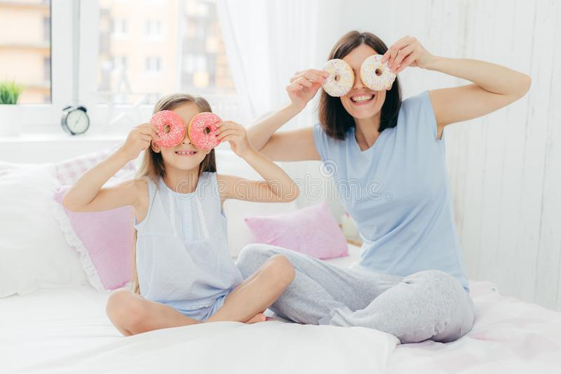 Familie, vrije tijds en samenhorigheidsconcept Gelukkige mum en het vrouwelijke kind, houden heerlijke doughnuts dichtbij ogen, d stock foto