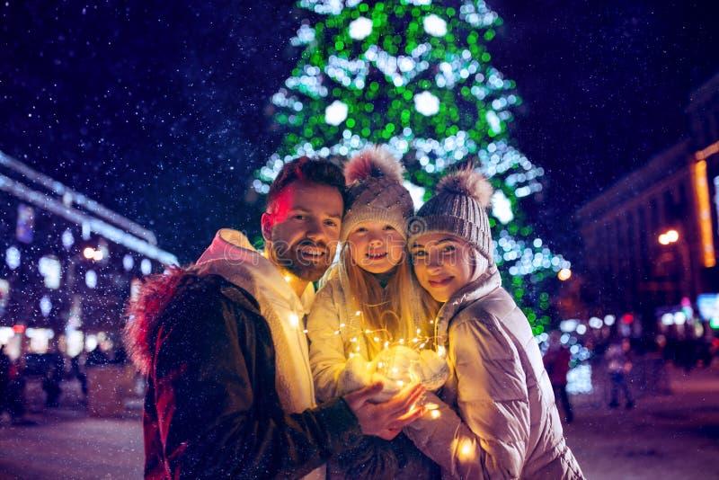 Familie, Weihnachten, Feiertage, Jahreszeit und Leutekonzept - glückliche Familie über Stadthintergrund und -schnee lizenzfreie stockbilder