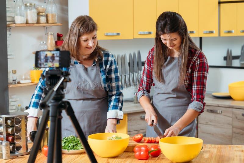 Familie, welche die Blogfrauen machen frischen Salat kocht lizenzfreie stockfotos