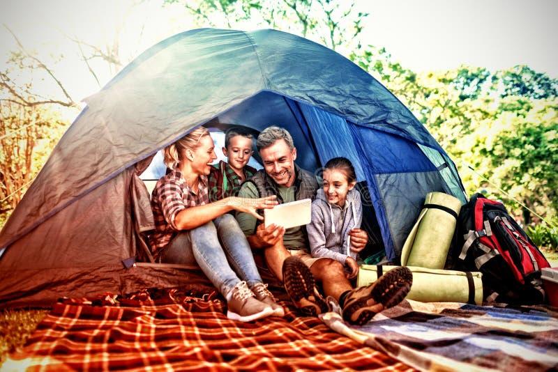 Familie, welche die digitale Tablette im Zelt betrachtet stockfotos