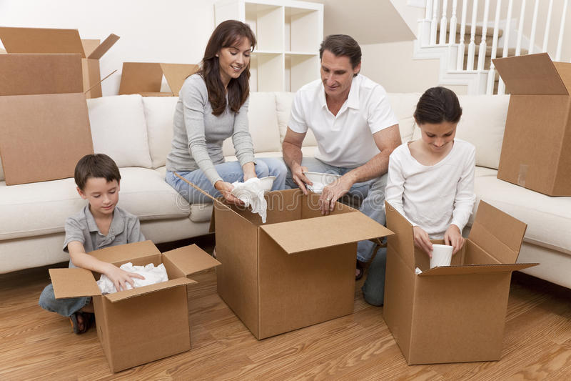 Familie, welche die Kästen verschieben Haus entpackt stockfoto