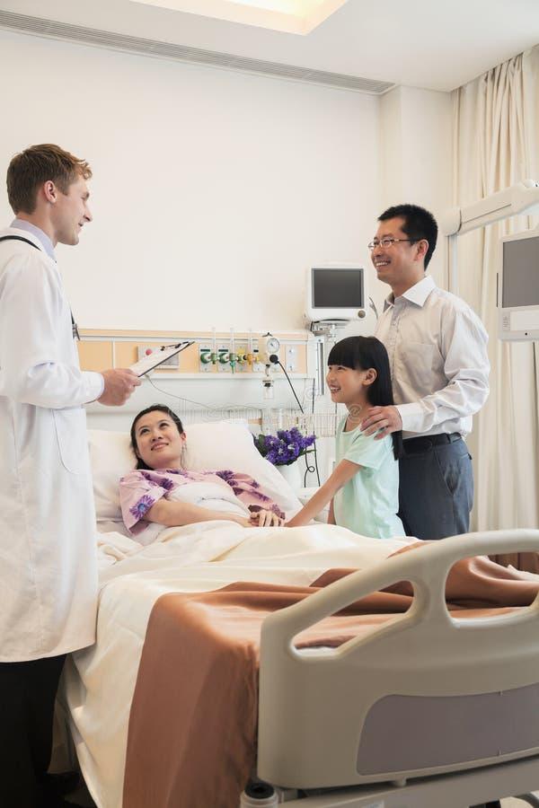 Familie, welche die Mutter im Krankenhaus, besprechend mit dem Doktor besucht lizenzfreie stockfotos