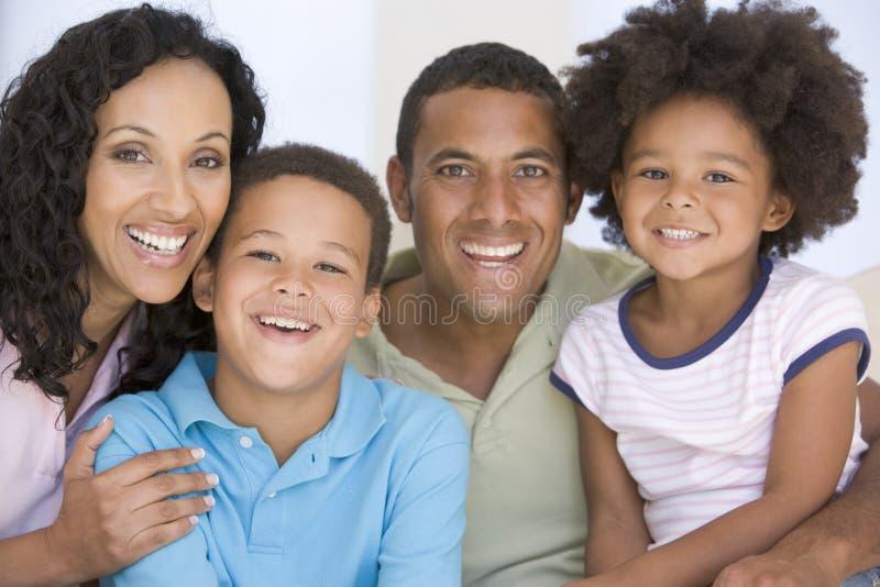 Familie in woonkamer het glimlachen stock foto's