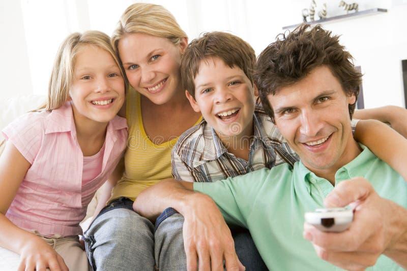 Familie in woonkamer met afstandsbediening stock afbeelding