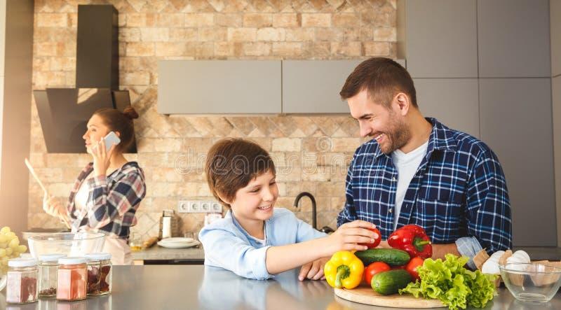 Familie zu Hause der Küche in der Vater- und Sohnstellung zusammen, welche die frohe Weilemutter des Spaßes spricht auf dem Sma stockfotografie