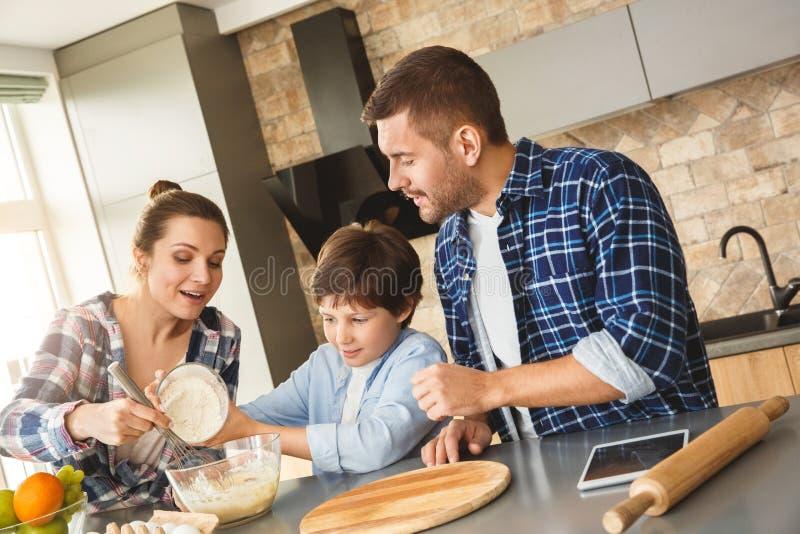 Familie zu Hause, die bei Tisch im helfenden Sohn der Mutter der Küche zusammen addiert Mehl, um zu rollen froh steht lizenzfreie stockfotografie