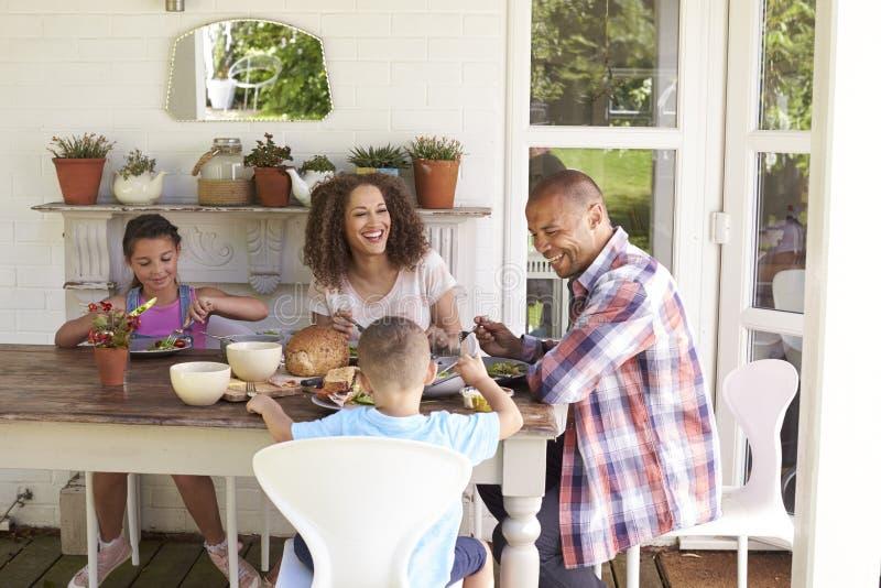 Familie zu Hause, die zusammen Mahlzeit im Freien isst stockfotos