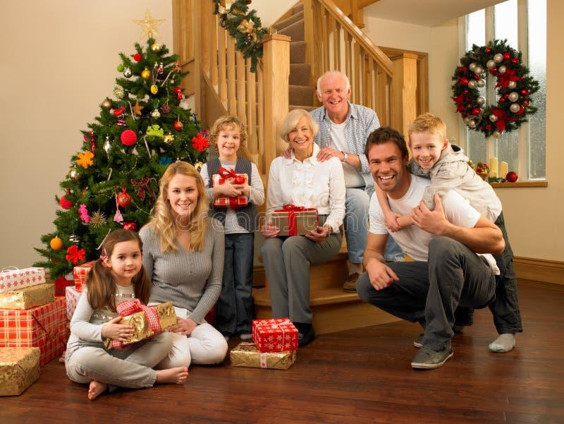 Familie zu Hause um Weihnachtsbaum stockfotografie