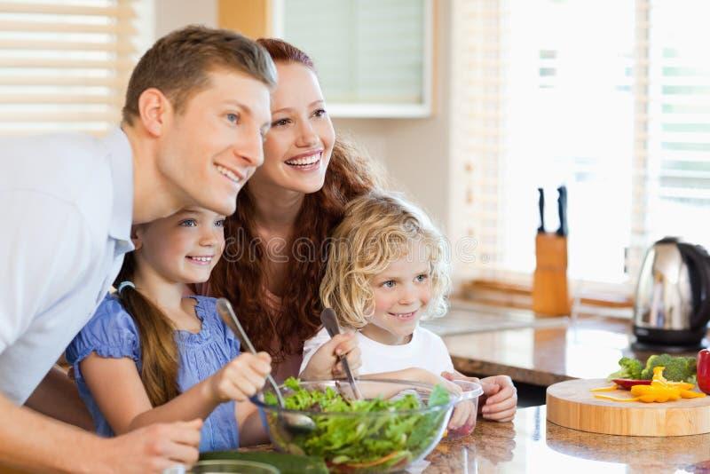 Familie zusammen mit Salat in der Küche stockfoto