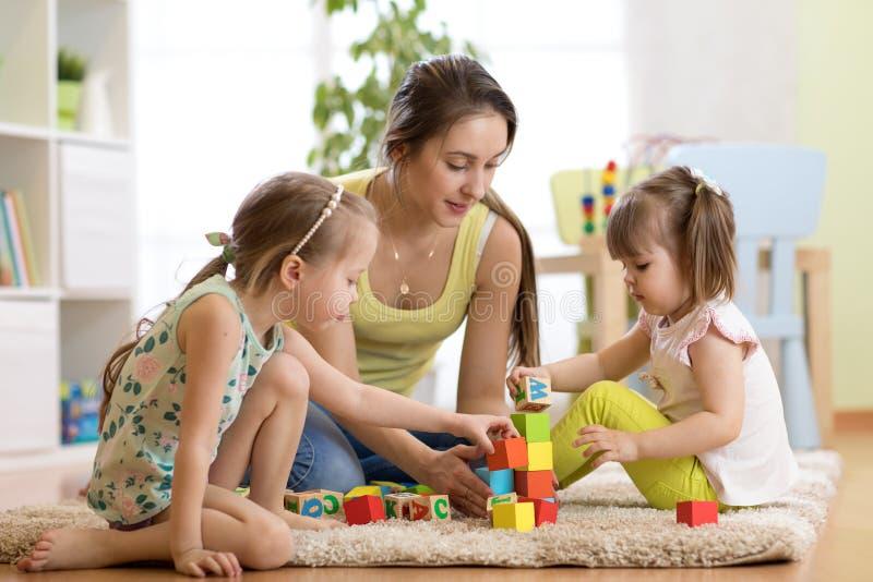 Familieactiviteiten in de kinderenruimte Moeder en haar jonge geitjes die op foor het spelen zitten stock foto's