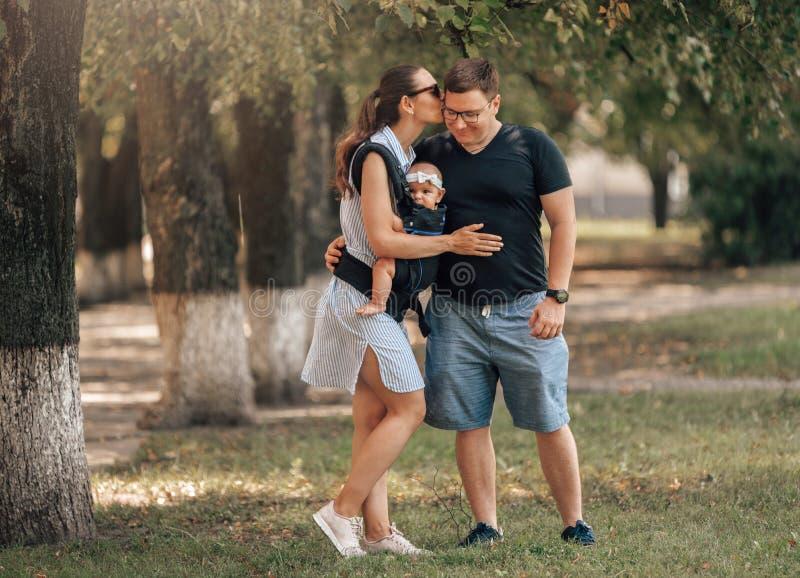 Familiedag in het park Gelukkig Jong Paar met Pasgeboren Baby De moeder vervoert baby in ergonomische babydrager stock fotografie