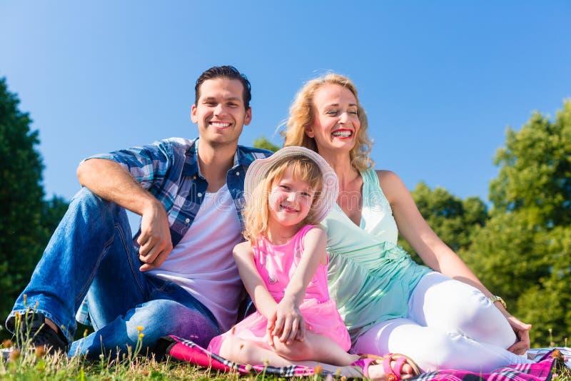 Familiefoto met vader, moeder en dochter in weide royalty-vrije stock afbeeldingen