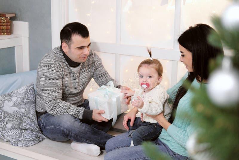 Familiemamma, papa en dochter thuis op de achtergrond van Kerstmisdecoratie en giften stock foto's