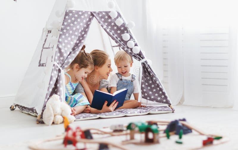 Familiemoeder die aan kinderenboek thuis lezen in tent royalty-vrije stock foto's