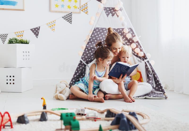 Familiemoeder die aan kinderenboek thuis lezen in tent stock foto