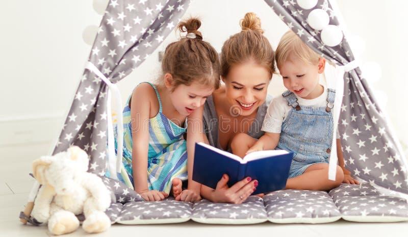 Familiemoeder die aan kinderenboek thuis lezen in tent stock afbeelding
