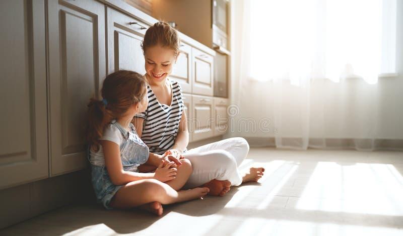 Familiemoeder en kinddochter die in keuken op vloer koesteren stock afbeeldingen