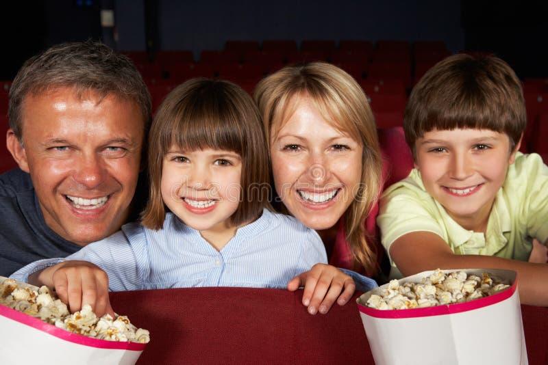 Familien-überwachender Film im Kino stockbild