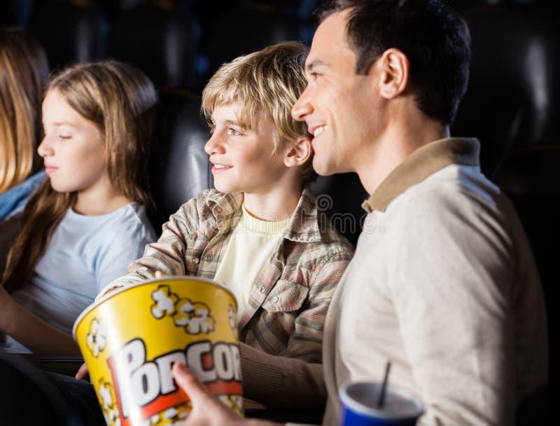 Familien-aufpassender Film im Kino-Theater stockbild