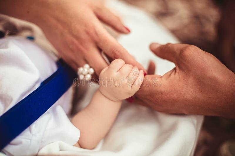 Familien-Baby-Hände Vater und Mutter, die neugeborenes Kind halten Kinderhandnahaufnahme in Eltern stockbild